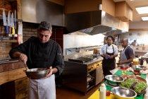Вид спереду крупним планом середнього віку Кавказького чоловічого шеф-кухаря змішування інгредієнтів в металеву миску в зайнята кухні ресторану, з іншими працівниками кухні, що працюють разом у фоновому режимі — стокове фото