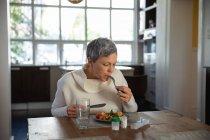 Vista frontale di una donna caucasica matura seduta a mangiare al suo tavolo da pranzo, con un bicchiere d'acqua, bottiglie di compresse e una scatola di pillole sul tavolo di fronte a lei — Foto stock