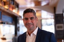 Ritratto ravvicinato di un gestore di un ristorante caucasico di mezza età elegantemente vestito sorridente alla telecamera in una cucina di un ristorante — Foto stock