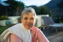 Портрет крупным планом взрослой белой женщины с короткими седыми волосами, сидящей в саду после упражнений, глядя в камеру и слегка улыбаясь, с полотенцем на плече — стоковое фото