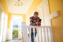 Вид спереди на улыбающуюся взрослую белую женщину с короткими седыми волосами, стоящую на посадочной площадке дома, опирающуюся на перила с помощью смартфона, окно с солнечным освещением на заднем плане с видом на сельскую местность — стоковое фото