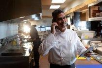 Vista frontal de cerca de un chef caucásico de mediana edad en el teléfono y sosteniendo una tableta en la cocina de un restaurante, un miembro del personal de la cocina que trabaja detrás de él - foto de stock