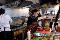 Боковой вид крупным планом молодой кавказской женщины-повара ladelling из соуса из банки в металлическую миску в кухне ресторана, с другими кухонными персоналами, работающими в фоновом режиме — стоковое фото