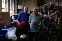 Porträt eines lächelnden älteren und mittleren Alters mit den Oberteilen zweier Hüte, die auf Geräten geformt wurden, neben denen sie in der Werkstatt einer Hutfabrik stehen — Stockfoto