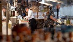 Вид со стороны белого шеф-повара средних лет и молодой афроамериканец, сотрудник кухни, работающий на занятой кухне ресторана — стоковое фото