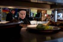 Вид спереди на молодую кавказскую шеф-повара на работе в оживленной ресторанной кухне, просматриваемой через полки, с другими кухонными работниками, работающими на заднем плане — стоковое фото