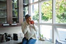 Vista frontal de una mujer caucásica madura con el pelo gris corto sentado en el mostrador en su cocina bebiendo una taza de café y mirando por la ventana, hay árboles afuera y el sol está brillando - foto de stock