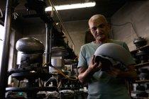 Vue de face gros plan d'un homme de course mixte senior tenant et inspectant le haut d'un chapeau qui a été façonné sur une pièce d'équipement dans l'atelier d'une usine de chapeaux — Photo de stock