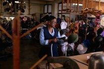 Vue de face d'une femme de race mixte d'âge moyen conduisant une machine pour nettoyer à la vapeur un chapeau qu'elle tient, debout à une table dans l'atelier d'une usine de chapeaux, d'autres chapeaux visibles en arrière-plan — Photo de stock