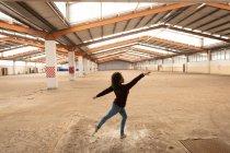 Вид сбоку на молодую балетную танцовщицу смешанной расы в джинсах и пуантах, танцующую с протянутыми на заброшенном складе руками — стоковое фото