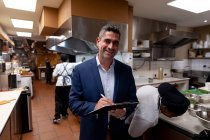 Portrait close up of a middle aged Caucasian male restaurant manager writing on a clipboard in a busy restaurant kitchen, while kitchen staff work in the background — Stock Photo