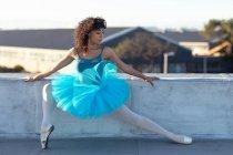 Vue de face d'une jeune danseuse de ballet mixte portant un tutu bleu tenant une position de ballet et regardant loin sur le toit d'un bâtiment urbain — Photo de stock