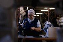 Зовнішній вигляд середнього віку змішана гонка жінка за допомогою швейної машини на капелюсі заводу, оточений матеріалами, бачили через обладнання — стокове фото