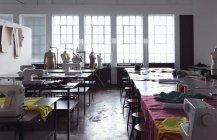 Vista frontal de mesas de trabalho com máquinas de costura e tecidos em um estúdio de design na faculdade de moda, com manequins na frente de uma janela no fundo — Fotografia de Stock