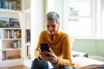 Plan d'accueil avant d'une femme caucasienne mûre avec le cheveu gris court s'asseyant à la maison dans son salon utilisant un smartphone, une fenêtre de soleil à l'arrière-plan — Photo de stock