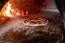 Fin de vue avant vers le haut d'une cuisson de pizza dans un four à pizza, avec les charbons chauds à l'arrière-plan — Photo de stock
