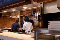 Вид спереду середнього віку Кавказький менеджер ресторану розмовляв з двома членами кухонного персоналу, видно зі спини, в ресторані кухні — стокове фото