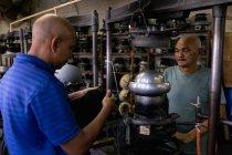 Seitenansicht eines älteren und eines mittleren Alters, die gemeinsam an einer Maschine in der Werkstatt einer Hutfabrik arbeiten. Der jüngere Mann hält einen Hut in der Hand, im Hintergrund ist Ausrüstung zu sehen. — Stockfoto