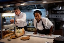 Front view close up of a middle aged Caucasian male chef checking orders at the order station while a young African American female chef stands waiting for food to be prepared for serving in a restaurant kitchen — Stock Photo