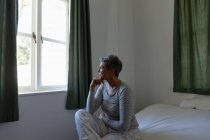 Side view close up of a mature Caucasian woman with short grey hair sitting on her bed and looking out of the window at home, with her hand on her chin — Stock Photo