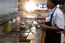 Вид збоку крупним планом молодого афроамериканського жіночого кухаря інгредієнти для смаження в каструлі в ресторані кухні — стокове фото