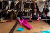 Вид спереди улыбающейся женщины средних лет, стоящей за столом, работающей с розовой тканью на шляпной фабрике . — стоковое фото