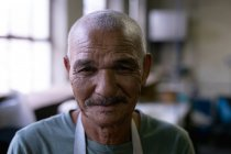 Retrato de perto de um homem de raça mista sênior olhando diretamente para a câmera e sorrindo na oficina em uma fábrica de chapéus — Fotografia de Stock