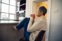 Side view close up of a mature Caucasian woman with short grey hair sitting on a chair in her kitchen with her feet up, drinking a cup of coffee and looking out of the window — Stock Photo