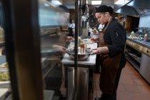 Vista lateral de perto de uma jovem chef caucasiana trabalhando em um balcão em uma movimentada cozinha do restaurante, com — Fotografia de Stock