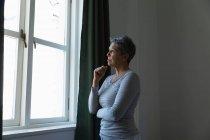 Vista lateral de una mujer caucásica madura con el pelo gris corto de pie y mirando por la ventana en casa - foto de stock