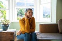 Vista frontal de cerca de una mujer caucásica madura con el pelo gris corto sentado en un sofá en su sala de estar mirando hacia otro lado con una expresión incierta, una ventana iluminada por el sol en el fondo - foto de stock