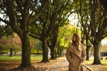 Mulher com as mãos no bolso andando no parque . — Fotografia de Stock