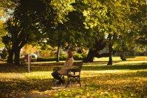 Mulher sentada em um banco no parque. — Fotografia de Stock