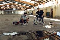 Вид спереди на двух молодых взрослых белых мужчин, сидящих на велосипедах BMX, разговаривающих друг с другом и использующих смартфоны на заброшенном складе — стоковое фото