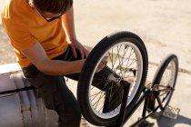Вид збоку людини носіння сонцезахисні окуляри сидять робить обслуговування колеса його BMX велосипеді зовні на сонці — стокове фото
