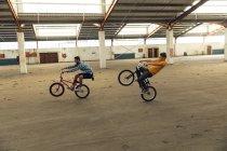 Вид сбоку на двух молодых белых мужчин, скачущих на задних колесах своих велосипедов BMX в заброшенном складе — стоковое фото