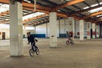 Vista frontal de dois jovens caucasianos andando de bicicleta BMX enquanto pratica truques em um armazém abandonado — Fotografia de Stock