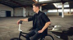 Вид збоку крупним планом молодий Кавказький чоловік, одягнений в чорний, сидячи на велосипеді BMX і дивлячись у занедбаному складі — стокове фото