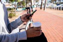 Vista laterale dell'uomo usando uno smartphone e tenendo in mano una tazza di caffè per strada — Foto stock