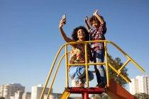 Вид спереди на молодую женщину смешанной расы и ее сына-подростка, наслаждающуюся временем вместе, играющую на детской площадке у моря, делающую селфи на горке в солнечный день — стоковое фото