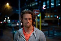 Portrait of a young Caucasian man in the street looking straight to camera during his late evening workout — Stock Photo