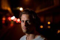 Retrato de um homem caucasiano novo na rua que olha à câmera na noite — Fotografia de Stock
