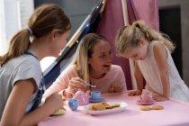 Vista frontal de una joven mujer caucásica con sus hijas adolescentes y más jóvenes teniendo una fiesta de té de muñecas en casa - foto de stock