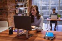 Вид спереди на молодую кавказку и женщину, работающую в офисе креативного бизнеса, сидящую за столом с ноутбуком, на заднем плане - коллега-мужчина, работающий за столом — стоковое фото