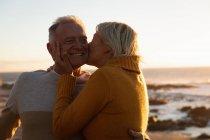 Вид сбоку: взрослый кавказский мужчина и женщина обнимаются и целуются у моря на закате — стоковое фото