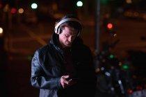 Vue de face d'un jeune homme caucasien debout dans une rue le soir écoutant de la musique avec un casque, tenant un smartphone — Photo de stock