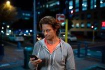 Fim da vista dianteira acima de um homem caucasiano novo que usa um smartphone com os auriculares sobre na rua durante seu exercício atrasado da noite — Fotografia de Stock
