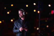 Vue de face d'un jeune homme caucasien debout dans une rue la nuit écoutant de la musique avec un casque allumé, tenant un smartphone — Photo de stock
