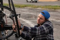 Вид збоку крупним планом молодого Кавказького чоловіка в інвалідному візку збірка лежачий велосипед і говорити по телефону на автостоянці — стокове фото
