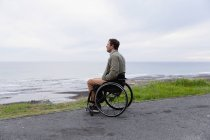 Side view of a young Caucasian man in a wheelchair enjoying a day out by the sea, enjoying the view — Stock Photo